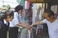 中学生が近隣の商店街を1軒1軒回り募金活動をしている