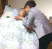在宅高齢者さまの手を取り、話しかける