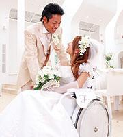 名刺に載せた「白い車椅子に乗ったうれしそうな新婦と、その新婦に優しくほほ笑む新郎」の写真