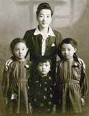 4歳のころ。母と姉と(中央が本人)
