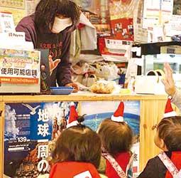 クリスマスに近所のお店にプレゼントを配る子どもたち