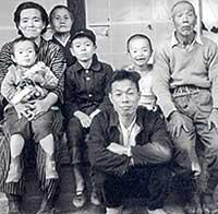 2歳のころ。左端で母に抱っこされているのが私。築100年以上経っていた自宅の縁側での家族写真。これが私の原点